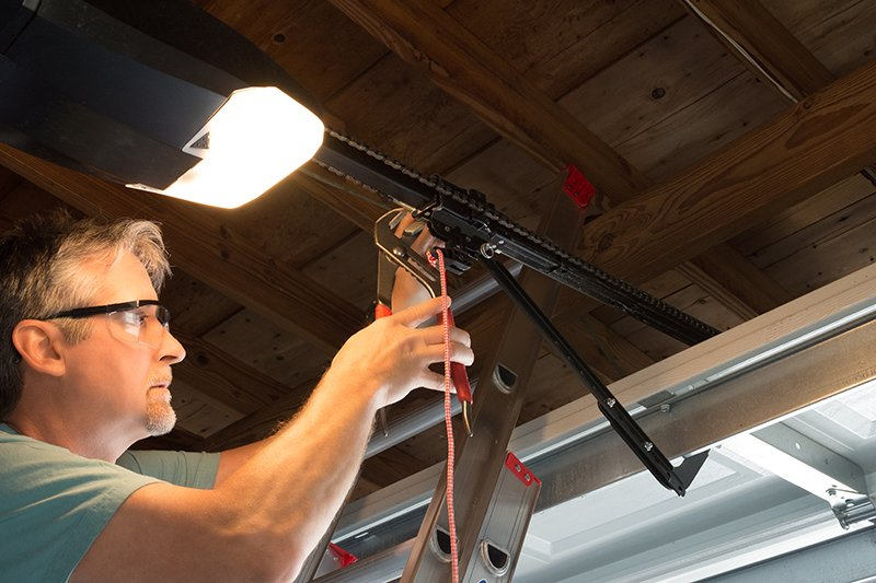 Closeup of a professional automatic garage door opener repair service technician man working on a ladder at a home residential location making adjustments and fixing it while installing it.